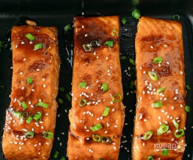 Готовую рыбку смажьте соусом, присыпьте кунжутом по вкусу и зеленым лучком.