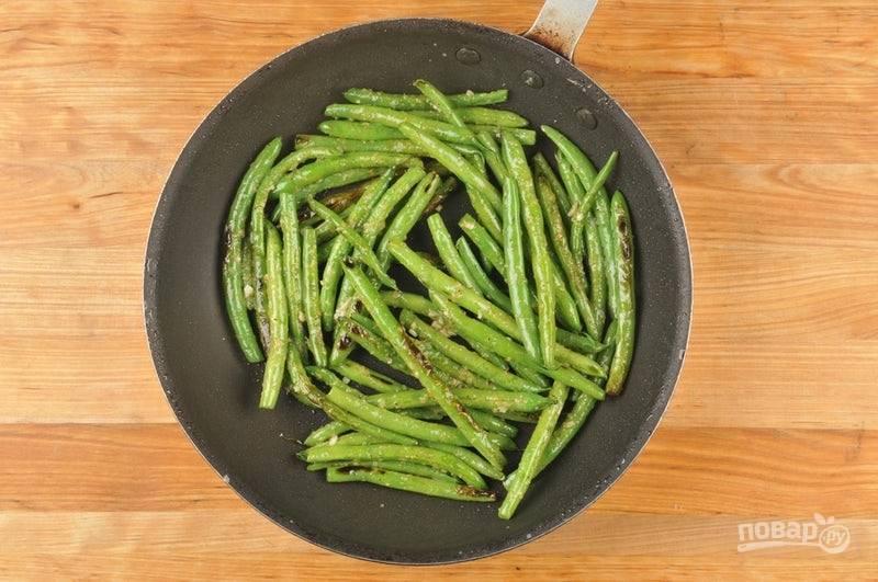 4. В это время займитесь гарниром. В сковороде разогрейте масло. Обжарьте в нём фасоль в течение 4-х минут, затем добавьте половину имбиря и чеснока. Перемешав, готовьте ещё 1,5 минуты.