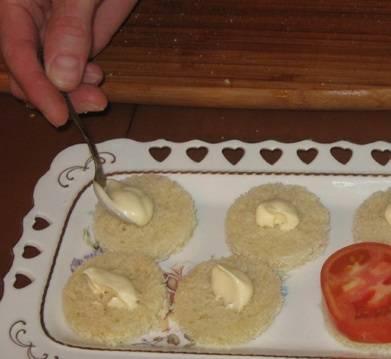 2. Смазываем каждый кусочек майонезом, и выкладываем тоненький кусочек помидора.