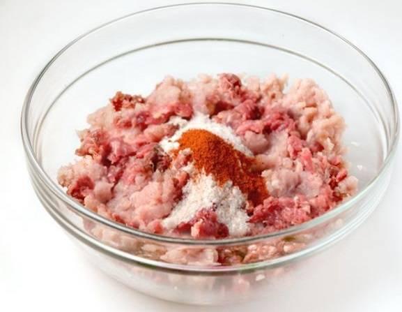 Смешиваем в емкости говяжий и свиной фарш. Сверху кладем столовую ложку соли и чайную ложечку красного перца.