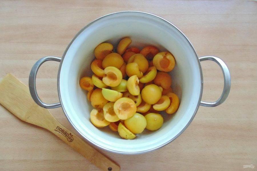 Разрежьте абрикосы на две части, и удалите косточки. Выложите в кастрюлю.