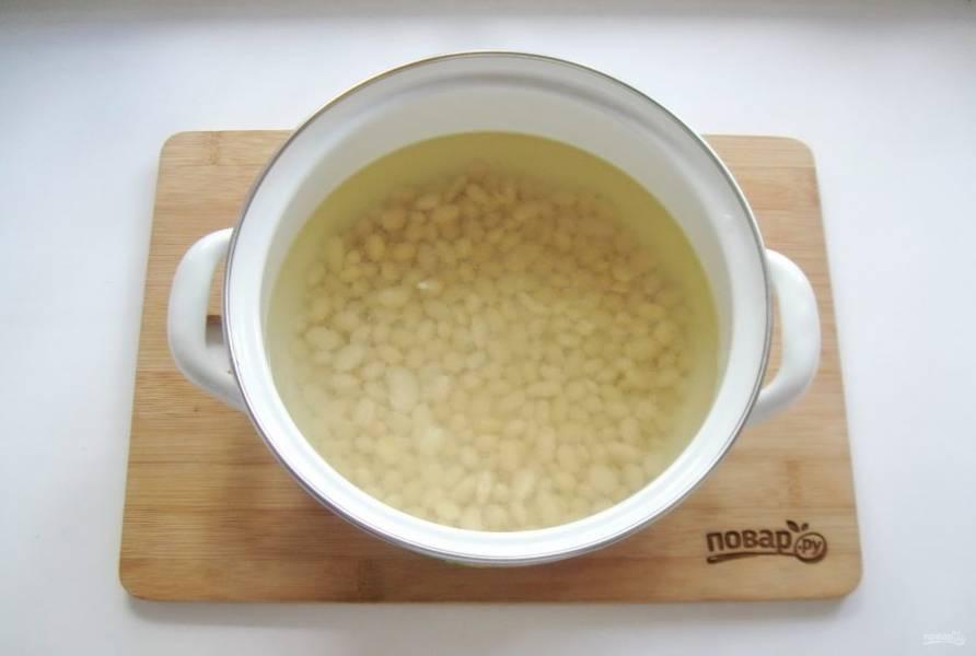 В кастрюлю выложите набухшую фасоль и залейте бульоном. Поставьте на плиту и варите 20-25 минут.