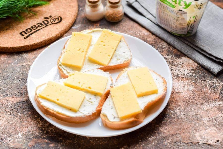Твердый сыр нарежьте ломтиками и выложите поверх хлеба.