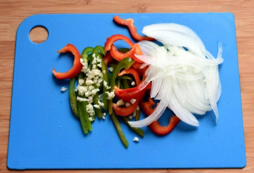 Подготовьте овощи. Промойте, обсушите и нашинкуйте тонкой соломкой лук и сладкий перец. Помидоры черри разрежьте пополам, петрушку крупно порубите. Чеснок измельчите.