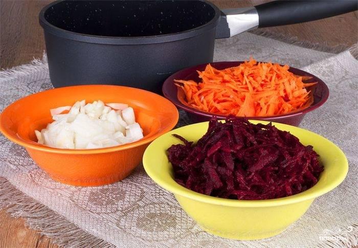 2.Для приготовления поджарки очищаем лук, морковь и свеклу. Луковицу нарезаем мелко, морковь и свеклу натираем на крупной терке, а чеснок измельчаем.