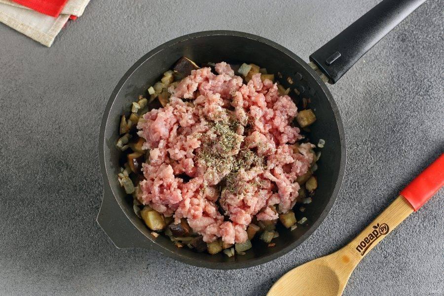 Когда баклажаны будут почти готовы, добавьте фарш, соль и специи. Готовьте все вместе периодически помешивая, пока фарш не побелеет.