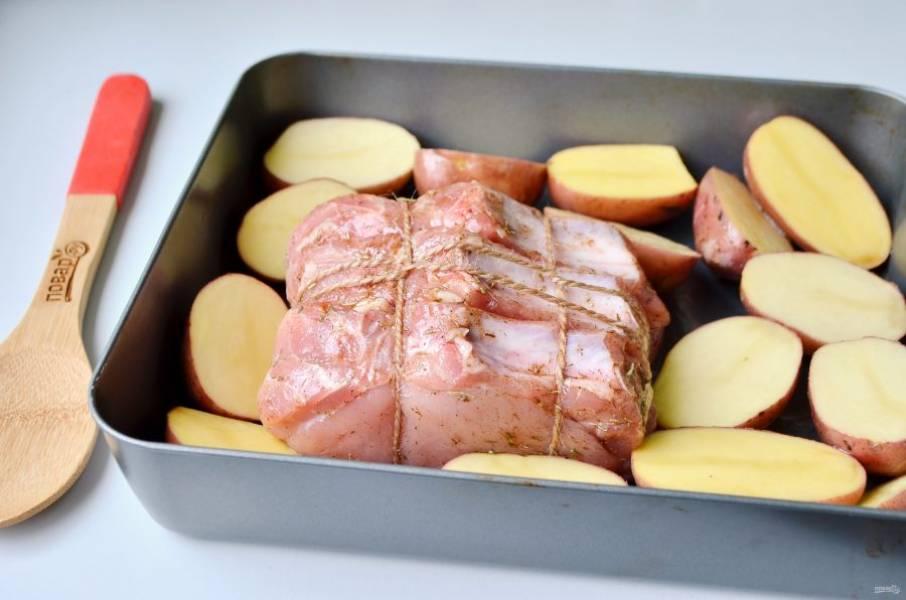 5. Прогрейте духовку до 200 градусов. Смажьте противень маслом растительным. Положите мясо (чеснок который был сверху и по бокам лучше убрать, чтобы не сгорел), вокруг положите картофель. Крупный картофель нужно порезать на 2 или 4 части, а мелкий можно оставить целым.