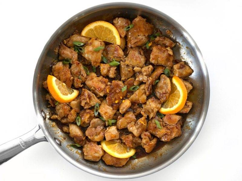 8.Помойте и измельчите зеленый лук, если остался апельсин, то нарежьте его дольками. Посыпьте зеленым луком мясо, выложите кусочки апельсина.