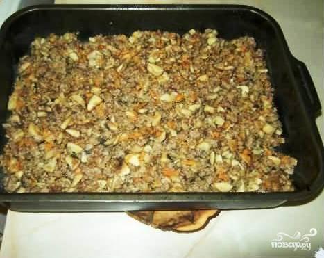 Берем форму для выпекания, выкладываем на дно начинку из грибов, овощей и фарша.