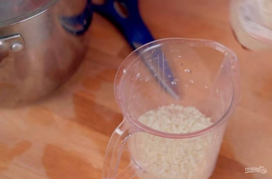 1. Для начала хорошо промойте рис до того, пока вода не станет полностью прозрачной. Далее залейте его холодной питьевой водой и дайте постоять примерно 20 минут, чтобы рис впитал в себя немного влаги.