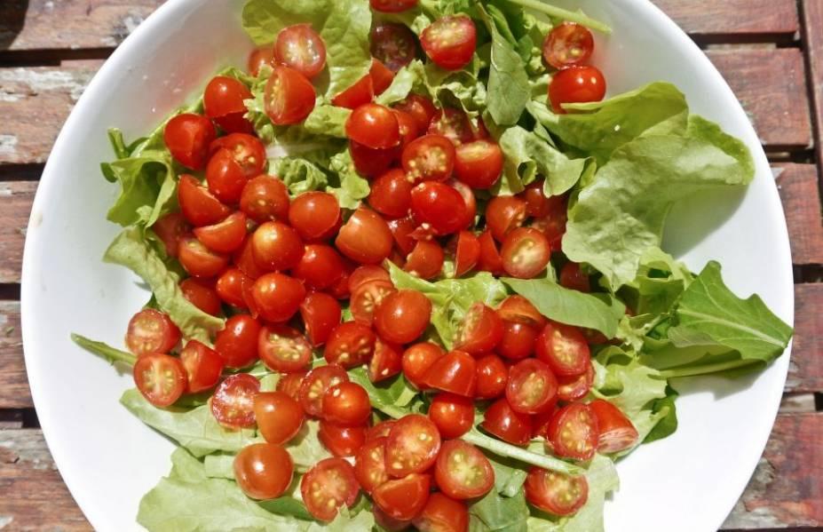 Листья салата вымойте и обсушите. Выложите их в миску для салата. Вымойте помидоры черри, разрежьте каждый томат на две части, положите их на листья салата.