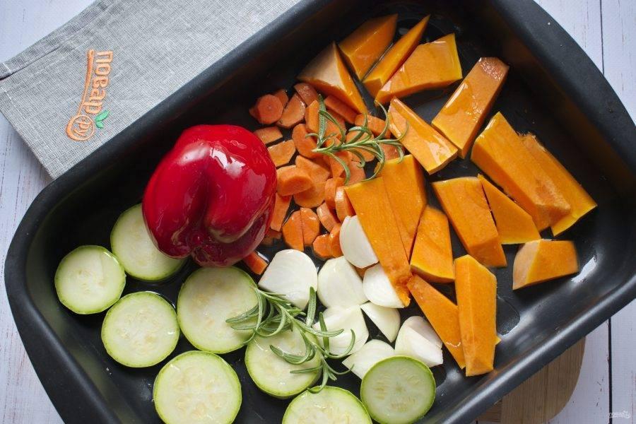 Кабачок, тыкву и лук нарежьте на средние куски. Морковь - тонкими кружками. Перец  оставьте целым, легче будет снимать кожицу после запекания. Выложите овощи на противень, брызните оливковым маслом, посолите и поперчите по вкусу.