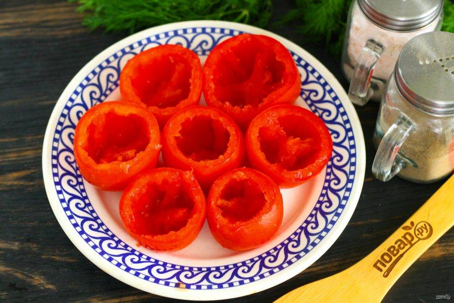 """Срежьте с томатов крышечки, чайной ложкой извлеките содержимое, оставляя лишь томатные """"бочонки"""". Если помидоры не хотят держаться на тарелке, срежьте и со дна овощей небольшую часть."""