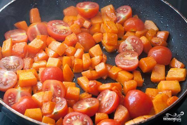 Добавляем к тыкве половинки помидоров черри, обжариваем еще минуту.