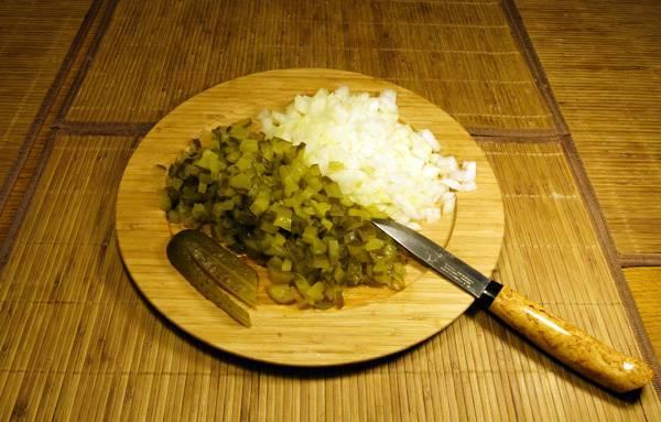 2. Огурцы нужно немного обсушить от маринада и нарезать мелкими кубиками. Также в рецепт приготовления пирожков с солеными огурцами можно использовать луковицу, также измельченную.