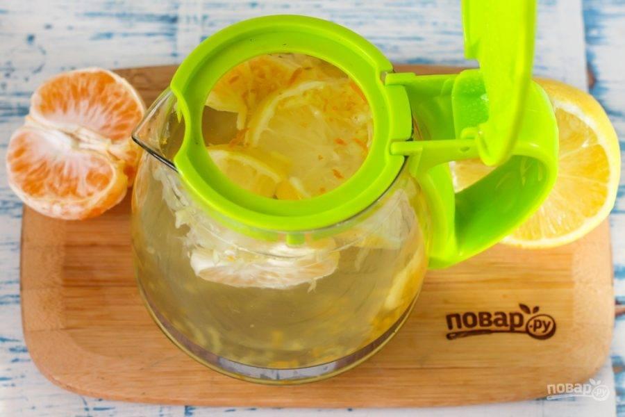 Залейте кипяток в заварник, закройте его крышкой и выдержите примерно 15 минут, затем аккуратно раздавите дольки мандарина и все перемешайте. Остудите напиток до 35 градусов.