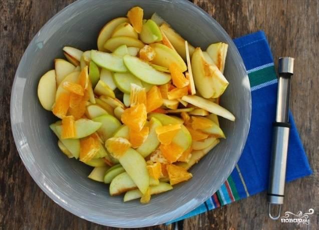 Яблоки промойте. Удалите из них сердцевину с семечками, а потом нарежьте тонкими дольками. Также нарежьте оставшуюся мякоть апельсина.