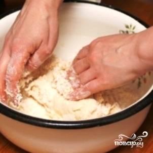 Небольшими порциями добавляем жидкую смесь к сухой, руками замешиваем тесто.