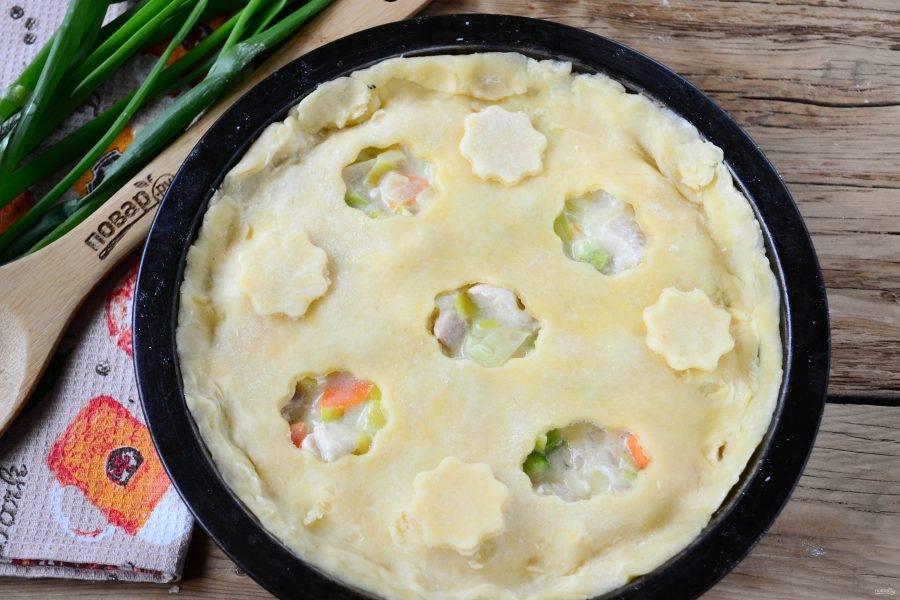 Вторую половину теста раскатайте и выложите на начинку. Сделайте несколько отверстий с помощью небольших вырубок для печенья, чтобы выходил пар. Отправьте пирог в духовку (температура — 200 градусов) на 30 минут или пока пирог сверху не подзолотится.