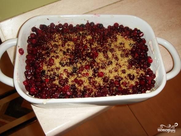 5. Духовку заранее разогрейте до 180 градусов. В форму выложите половину творога, а сверху - вымытые и обсушенные ягодки. Можно присыпать их небольшим количеством сахара.