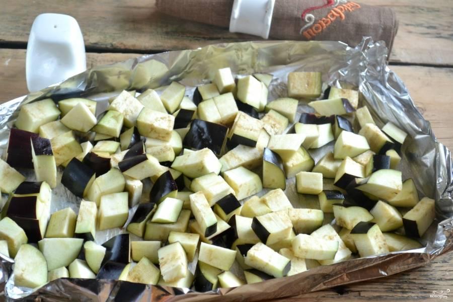 Баклажаны порежьте среднего размера кубиками, заверните в фольгу и отправьте в разогретую духовку на 15 минут.