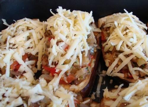 Овощи соедините с грибами, перемешав их. Полученной начинкой наполняем лодочки из баклажанов, сверху присыпав тертым сыром. Запекаем еще 15 минут, пока не расплавится сыр. Приятного аппетита!