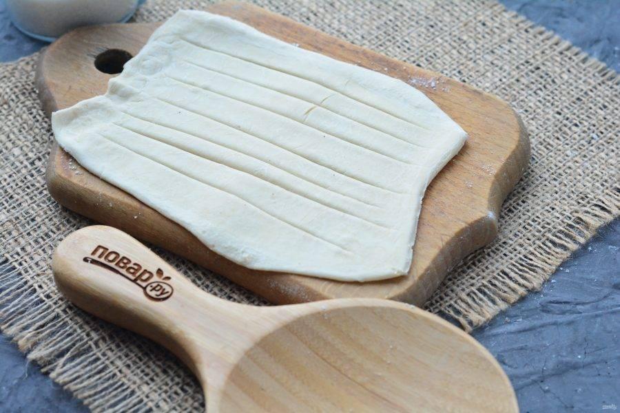 Слоеное тесто разрежьте на прямоугольники, каждый раскатайте скалкой. В середине сделайте надрезы, не доходя до краев.