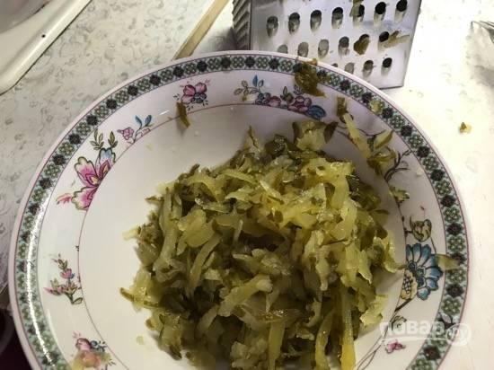 5. Соленые огурцы также натрите на крупную терку и отожмите лишнюю жидкость. Выложите слоем поверх картофеля.