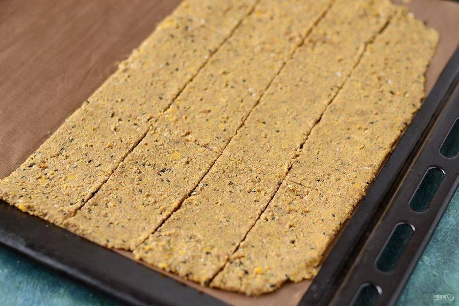 Выложите получившуюся массу толщиной 3-4 мм. на силиконовый коврик или лист для выпечки. Разрежьте на прямоугольники. Отправьте хлебцы в духовку на 2,5-3 часа при температуре 120 градусов.