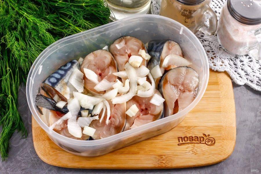 Промойте тушку скумбрии в воде внутри и снаружи, нарежьте порционными кусочками. Очистите луковицу от кожуры, промойте в воде и нарежьте полукольцами. Выложите луковый слой на дно контейнера или банки. На лук выложите рыбную нарезку.