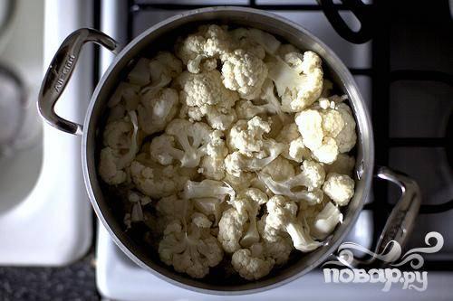 1. Очистить лук. Натереть сыр. Нарезать розмарин и базилик. Разогреть духовку до 175 градусов. Измельчить цветную капусту на средние цветки. Добавить в кастрюлю с чайной ложкой соли, залить водой и кипятить на медленном огне 15-20 минут, пока капуста не станет мягкой. Слить воду и откинуть на дуршлаг, дать постоять несколько минут, чтобы вода стекла, и капуста остыла.