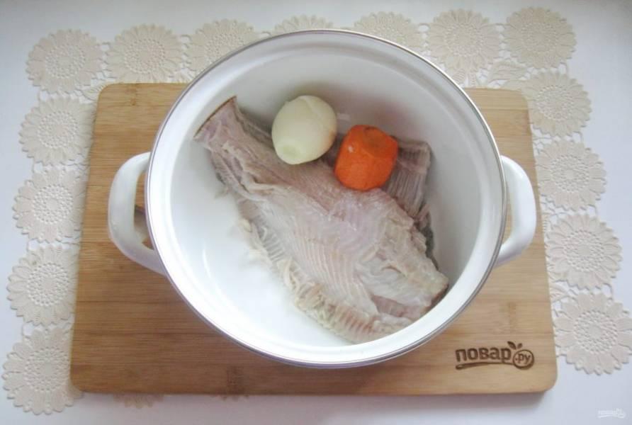 Выложите камбалу в кастрюлю. Добавьте лук и морковь.