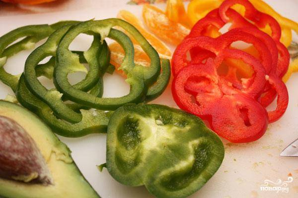 Перцы разного цвета нарезаем плоскими кольцами - как на фотографии. Выкладываем поверх авокадо и апельсинов.