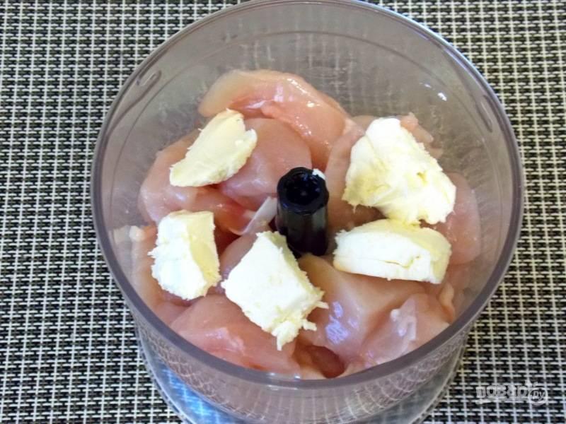 Куриную грудку вымойте и обсушите. Порежьте на кусочки, добавьте масло и пробейте блендером до однородной массы.