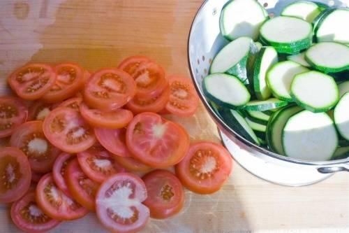 Далее промываем под проточной водой помидоры, высушиваем кухонным полотенцем и выкладываем на разделочную доску. Острым ножом нарезаем их на красивые кружочки с толщиной около 5 миллиметров и выкладываем их в отдельную тарелку.