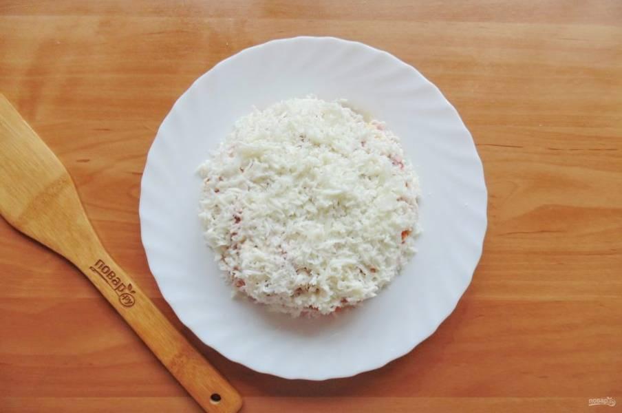 Яйца сварите вкрутую, охладите и очистите. Отделите белки от желтков. Натрите белки на терке и покройте весь салат.
