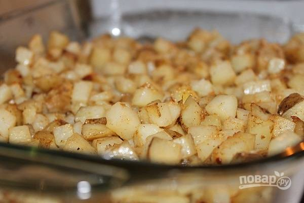 1. Картофель вымойте, очистите и нарежьте небольшими кубиками. Посолите, добавьте специи по вкусу и растопленное сливочное масло. Все тщательно перемешайте и выложите в жаропрочную форму. Отправьте в разогретую до 200 градусов духовку. Запекайте около получаса, каждые 10 минут перемешивая.