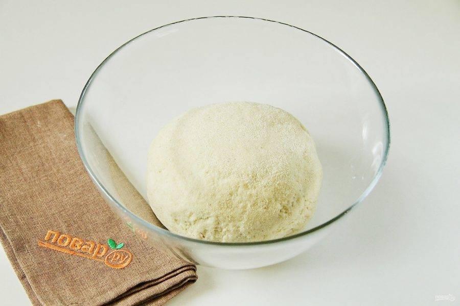 Переложите тесто на стол, присыпанный манной крупой. Месите тесто руками, по мере необходимости подсыпая еще манку, пока оно не перестанет липнуть к рукам. Соберите его в шар, положите в миску, накройте пленкой и уберите в теплое место примерно на час.