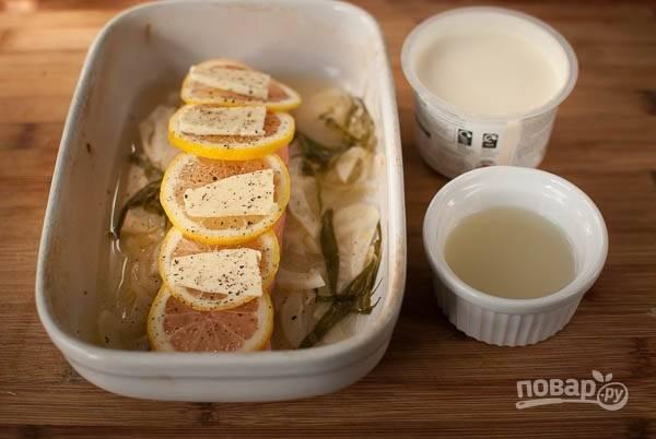 Теперь в форму уложите рыбку. На нее — кружочки лимона и кусочки масла, также в форму добавьте сметану и бульон.