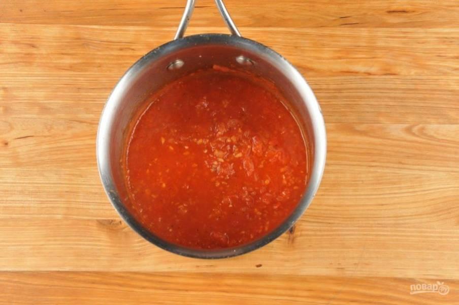 2. Теперь сделайте соус. В сотейнике разогрейте масло. Обжарьте в нём в течение 1-ой минуты измельчённый лук с чесноком. Затем добавьте помидоры. Готовьте на среднем огне ещё 2 минуты. Далее влейте пасту и воду, всыпьте перец и соль. Доведите соус до кипения и варите 2,5 минуты, помешивая.