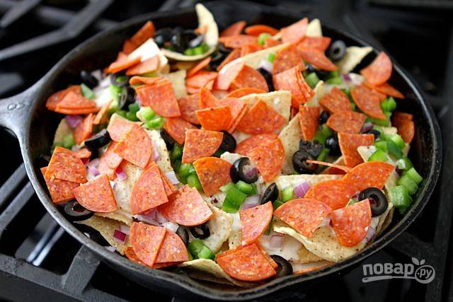 5. Сверху начините чипсы нарезанными на кусочки салями, сладким перцем, луком, маслинами и натертым сыром.