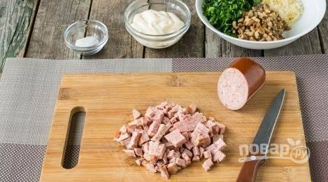 Мелко нарежьте колбасу, промытый зелёный лук и петрушку.