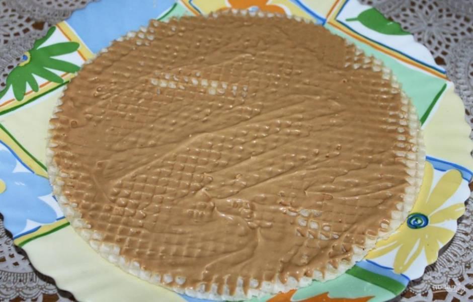 Первую вафлю смажьте кремом на тарелке для подачи торта.