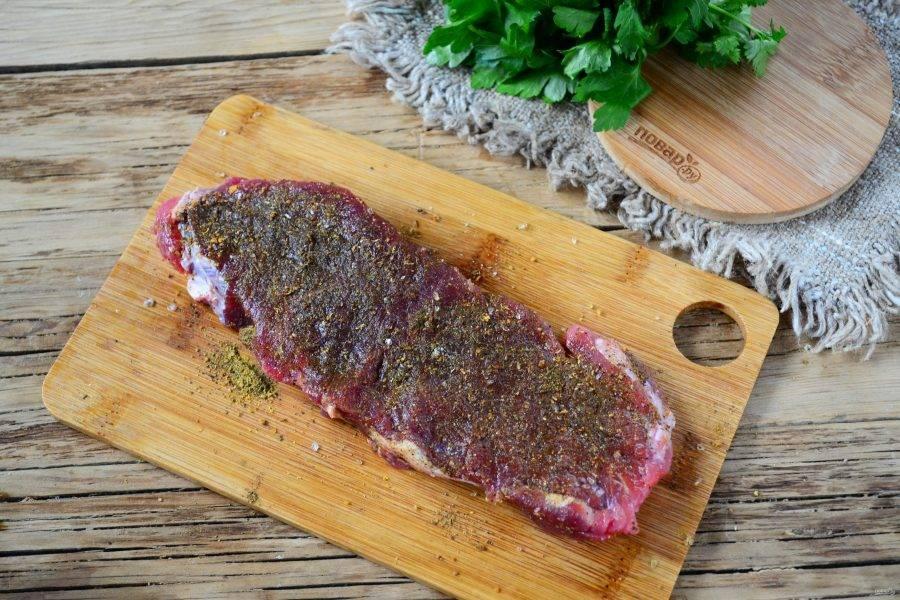 Натрите стейк солью, перцем, чесночным порошком и кайенским перцем. Хорошенько помните мясо, чтобы специи максимально проникли вовнутрь.