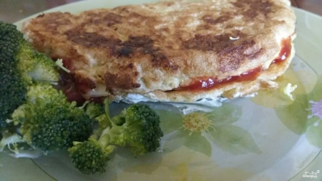 Подготовьте начинку для овсяноблина. Здесь я использую небольшие кусочки белого сыра и помидоры, нарезанные кружочками. Уложите сыр, а затем и помидоры, на одну половинку блина, а второй накройте. По необходимости немного прогрейте блин, чтобы сыр расплавился. Теперь блюдо можно подавать.