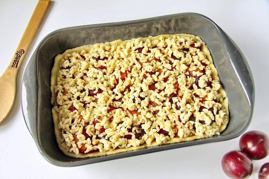 Подмерзшее тесто натрите на крупной терке поверх слив. Выпекайте в духовке при температуре 180 градусов около 40 минут.