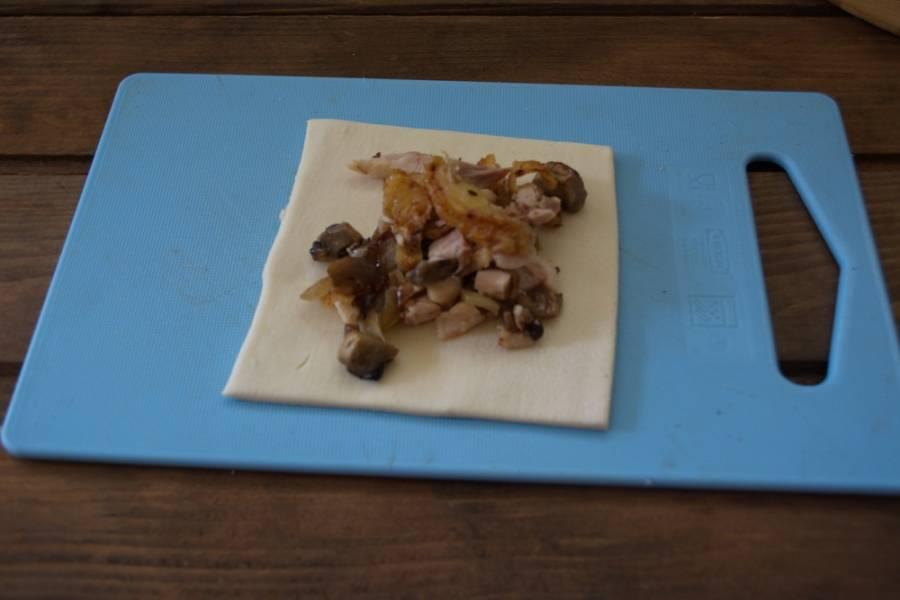 Куриное мясо запекаем в духовке. Снимаем с кости. Я шкурку удалила, ибо считаю ее не полезной.  Раскатайте слоеное тесто. Нарезаем на квадраты. На каждый выкладываем начинку из лука, шампиньонов и куриного мяса.