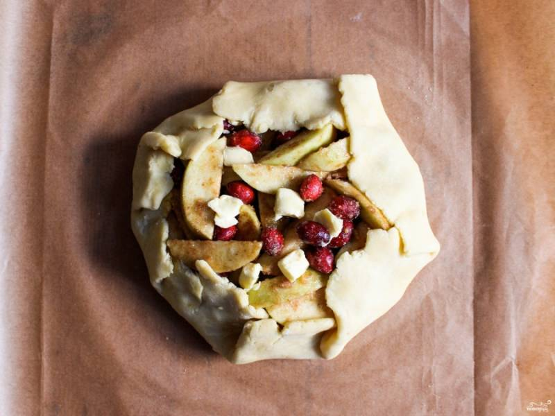 2. Яблоки и бруснику моем, яблоки ржеем кусочками. В сотейнике смешаем с сахаром, крахмалом, корицей и добавим масло. Ставим на маленький огонь и мешаем, пока все не смешается. Мешайте аккуратно. чтобы ягоды не повредились. Выкладываем начинку на тесто и немного завернем края, чтобы получились бортики.