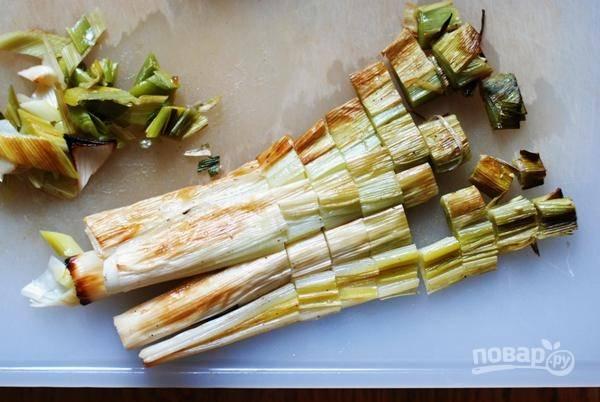 Стебли лука разрежьте напополам вдоль. Положите лук на противень срезом вниз, сбрызните маслом, присыпьте солью. Запекайте 12 минут, после достаньте, остудите и нарежьте лук мелко.