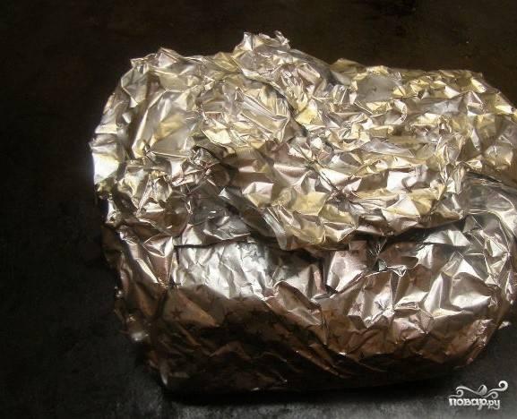 5.Нагрейте духовку до 190 С. Кусок мяса аккуратно заверните в фольгу. Постарайтесь, чтобы образовавшийся в процессе приготовления сок и жир не стекал в противень, а оставался в фольге вместе с мясом. Это позволит продукту оставаться сочным во время приготовления. Поставьте мясо в разогретую духовку. В течение 2 часов мясо должно запечься.